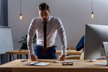 serious businessman standing and leaning on working table