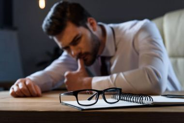 tired pensive businessman leaning on table with glasses on foreground