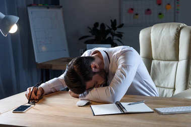 tired businessman sleeping at working table