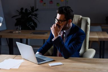 serious businessman sitting in dark office and yawning