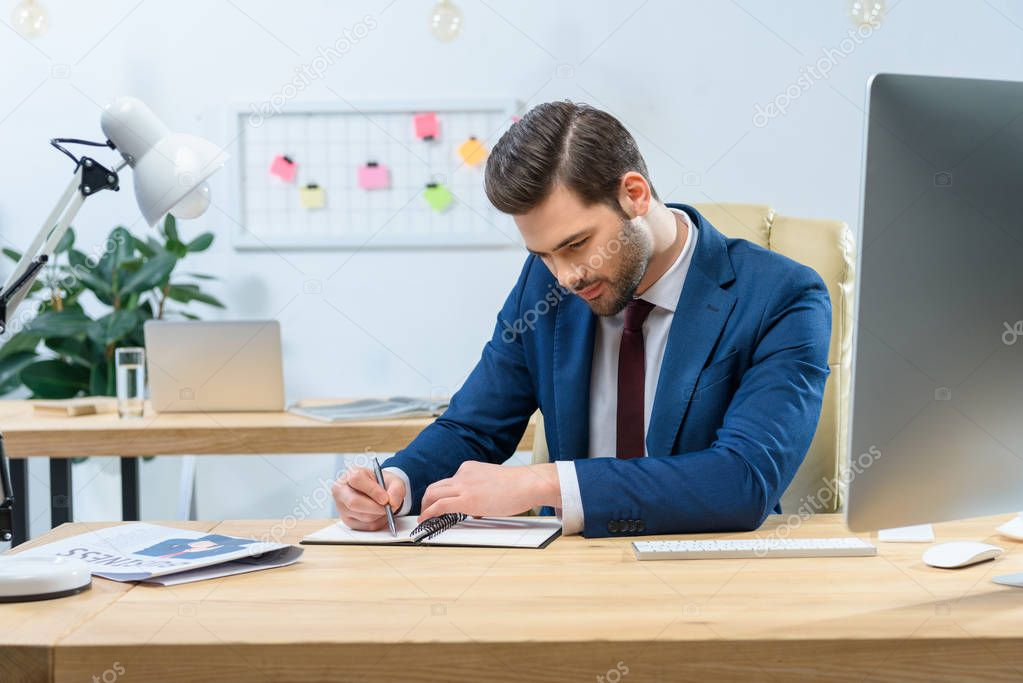 handsome businessman writing something to notebook at table