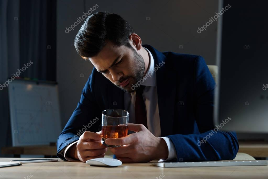 tired drunk businessman looking at glass of whiskey in office
