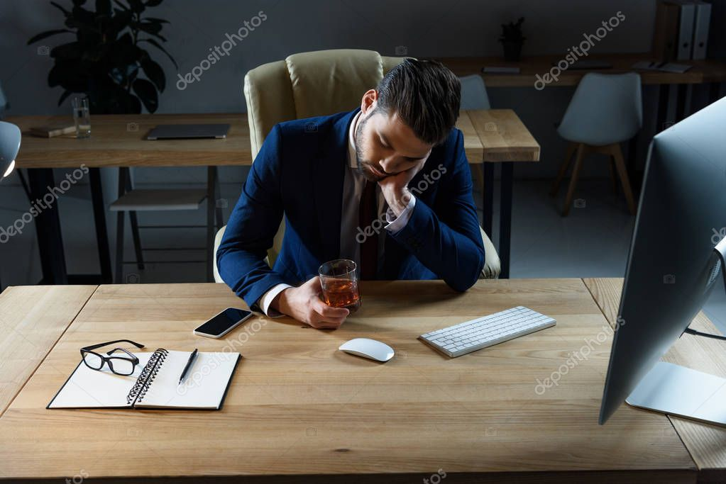tired drunk businessman sitting with glass of whiskey in office