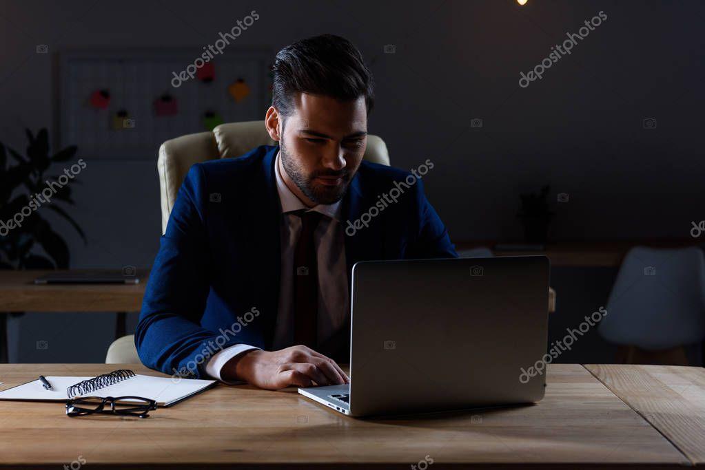 handsome businessman working at laptop in dark office