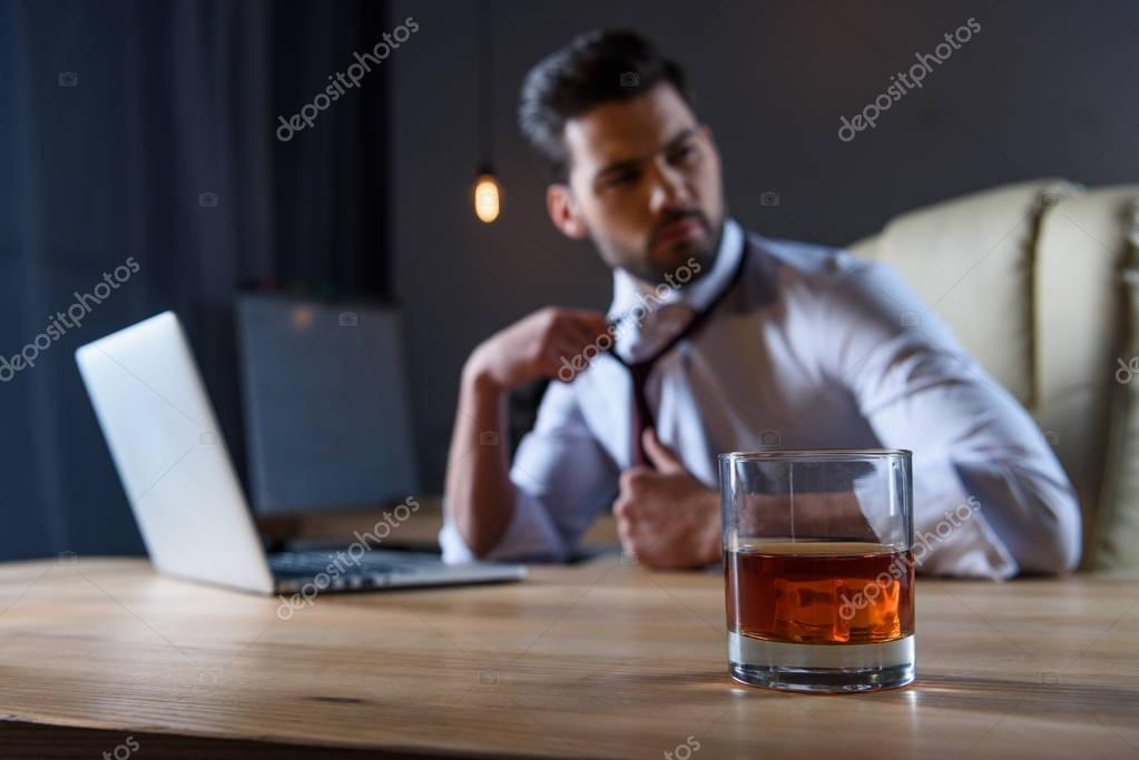 tired businessman loosen tie and sitting at table with glass of whiskey on foreground