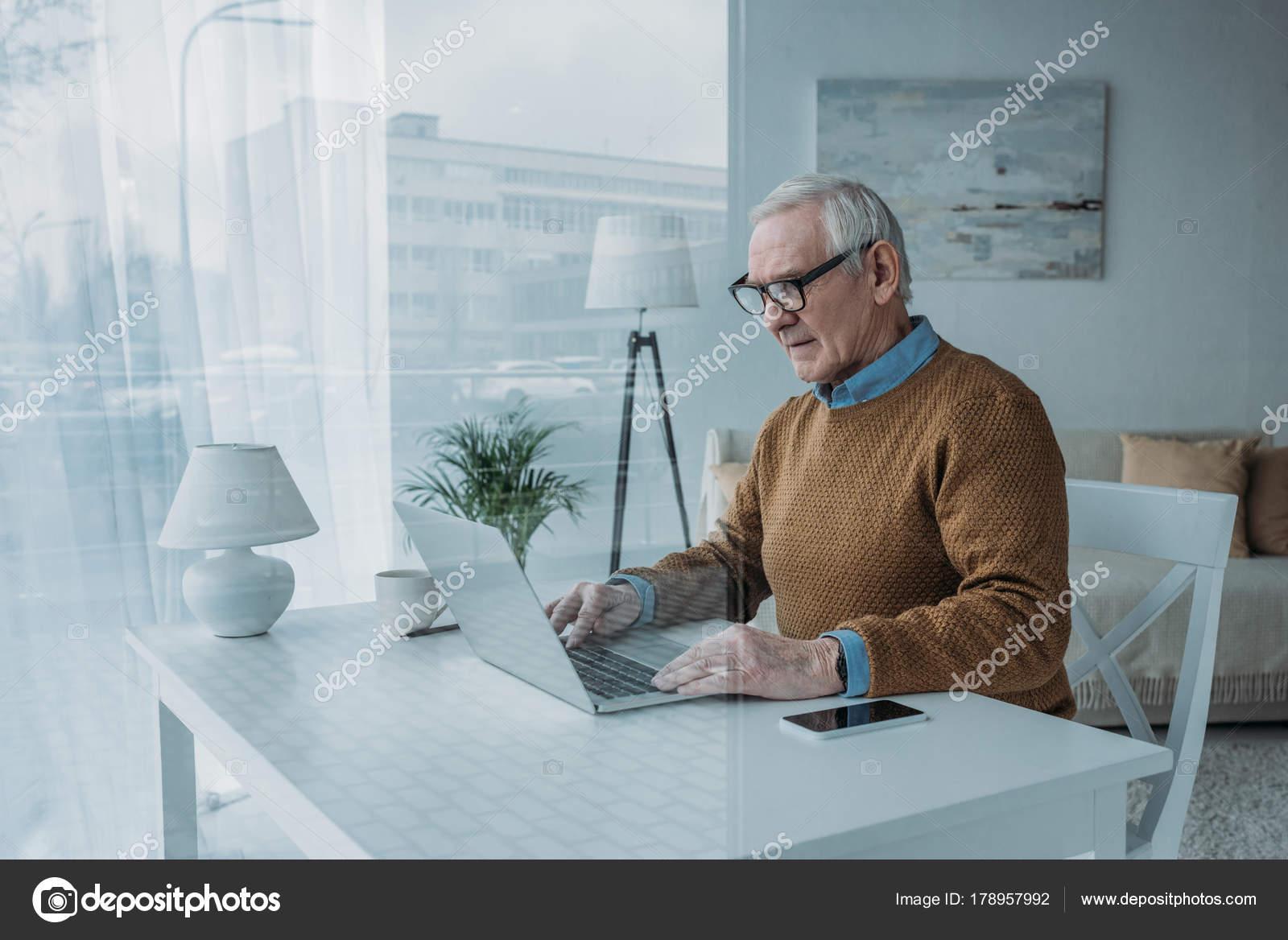 derri re vue verre senior homme confiant travaillant sur ordinateur portable photographie. Black Bedroom Furniture Sets. Home Design Ideas