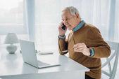Senior beschäftigt Mann arbeitet am Laptop und telefoniert