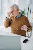 Älterer Mann wird müde von der Arbeit am Laptop