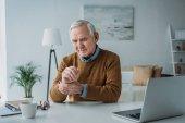 Senior arbeitet am Laptop und überprüft seinen Puls