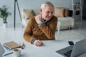 Starší muž pracuje na notebook trpící bolesti zad