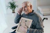 Senior man feels nostalgic while holding photo in frame