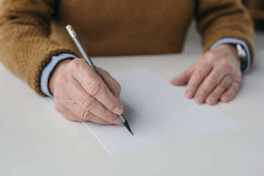 Close-up view of senior man writing on blank paper