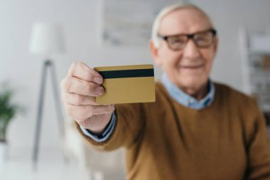 Senior smiling man holding credit card