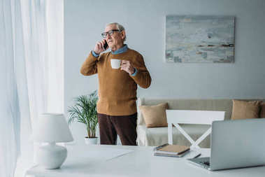 Senior confident man with coffee cup working in office and making phone call