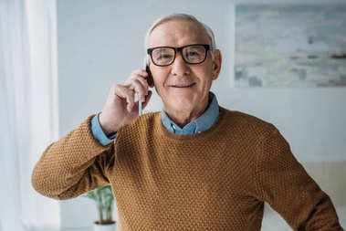 Elder smiling man working in office and making phone call