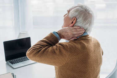 Elder man working in office and suffering from pain in neck