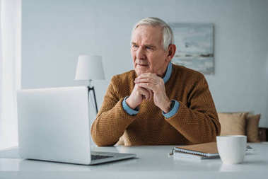 Senior confident man working on laptop