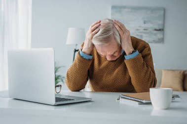Senior man working in office and suffering from headache