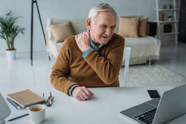 Senior man working on laptop suffering from back pain