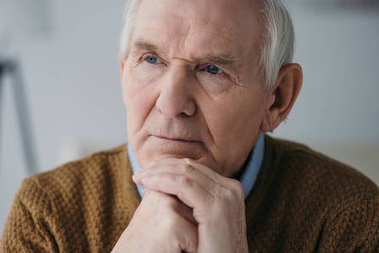 Senior thoughtful man leaning on hands in light room