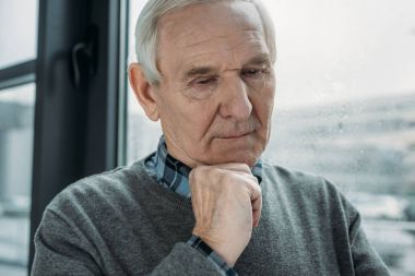 Senior thoughtful man with sad expression cries