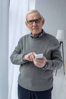 Senior confident man in eyeglasses using smartphone
