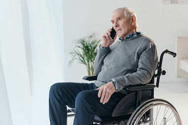 Senior man in wheelchair making a phone call in empty room