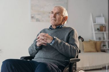 Senior thoughtful man in wheelchair in empty room
