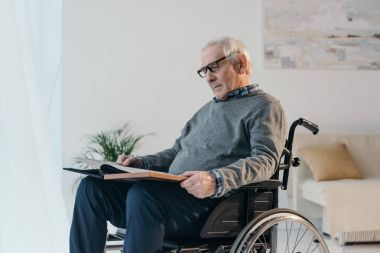 Senior man in wheelchair looks at old photo album