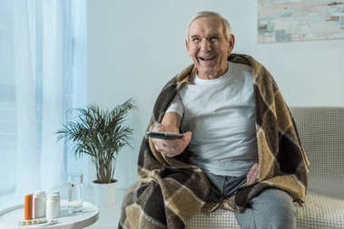 Senior man covered in plaid watches tv during sickness in room with medications on table