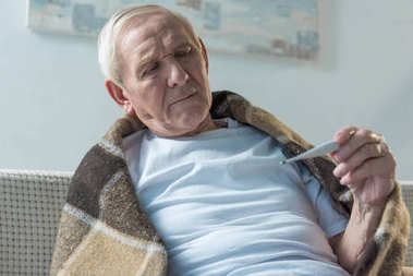Senior sick man covered in plaid sitting on sofa and checking thermometer