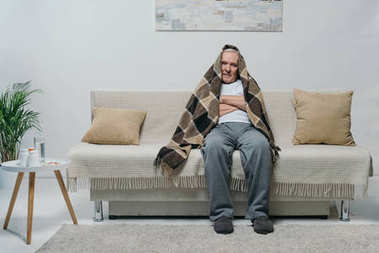 Senior chilled man covered in plaid sitting on sofa
