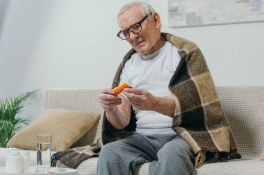 Senior man in eyeglasses and plaid looks at pill bottle stock vector
