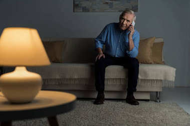 Senior confident man making a phone call in empty room