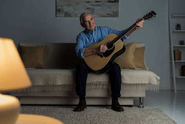Senior happy man plays acoustic guitar while sitting on sofa in room