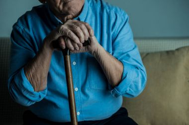 Close-up view of senior man leans on a cane while sitting on sofa