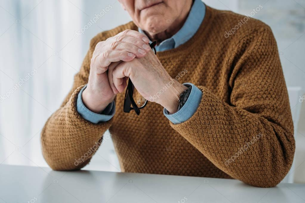 Serious senior thoughtful man sitting by the desk in light room