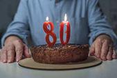 Fotografie Vergrößerte Ansicht des senior woman 80 Jubiläum mit Kuchen und Anzahl Kerzen brennen