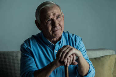 Senior sad man leans on a cane while sitting on sofa