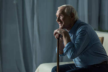 Senior smiling man leans on a cane while sitting on sofa