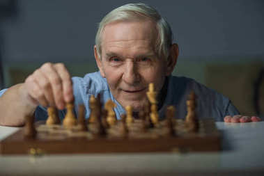 Senior smiling man playing chess board game