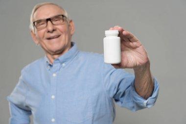 Senior confident man holds white bottle of pills isolated on gray background