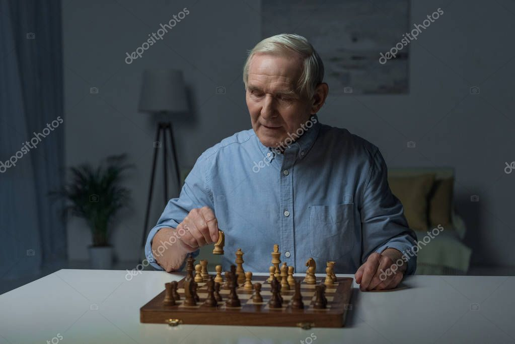 Senior confident man playing chess board game
