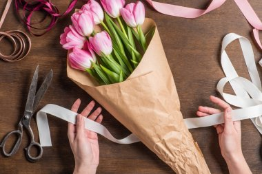 Pink tulips and hands with ribbon
