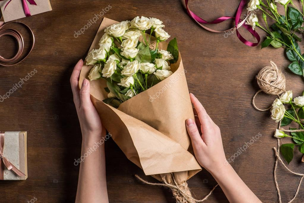 hands holding roses bouquet