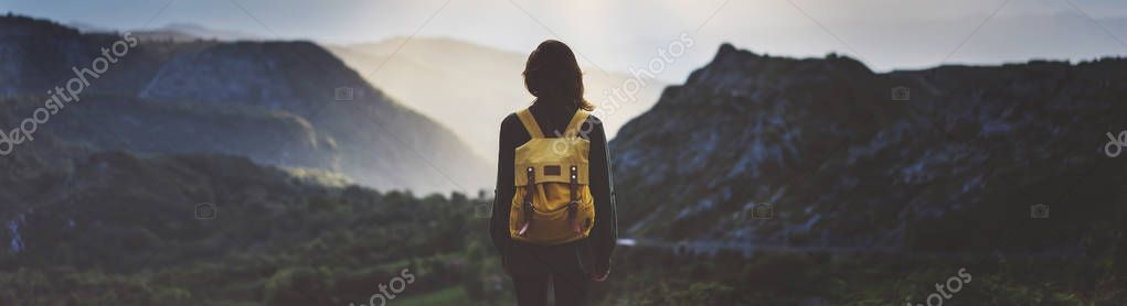 Hipster young girl with bright backpack enjoying sunset on peak of foggy mountain. Tourist traveler on background valley landscape view mockup. Hiker looking sunlight flare in trip in northern spain basque country Picos de Europa