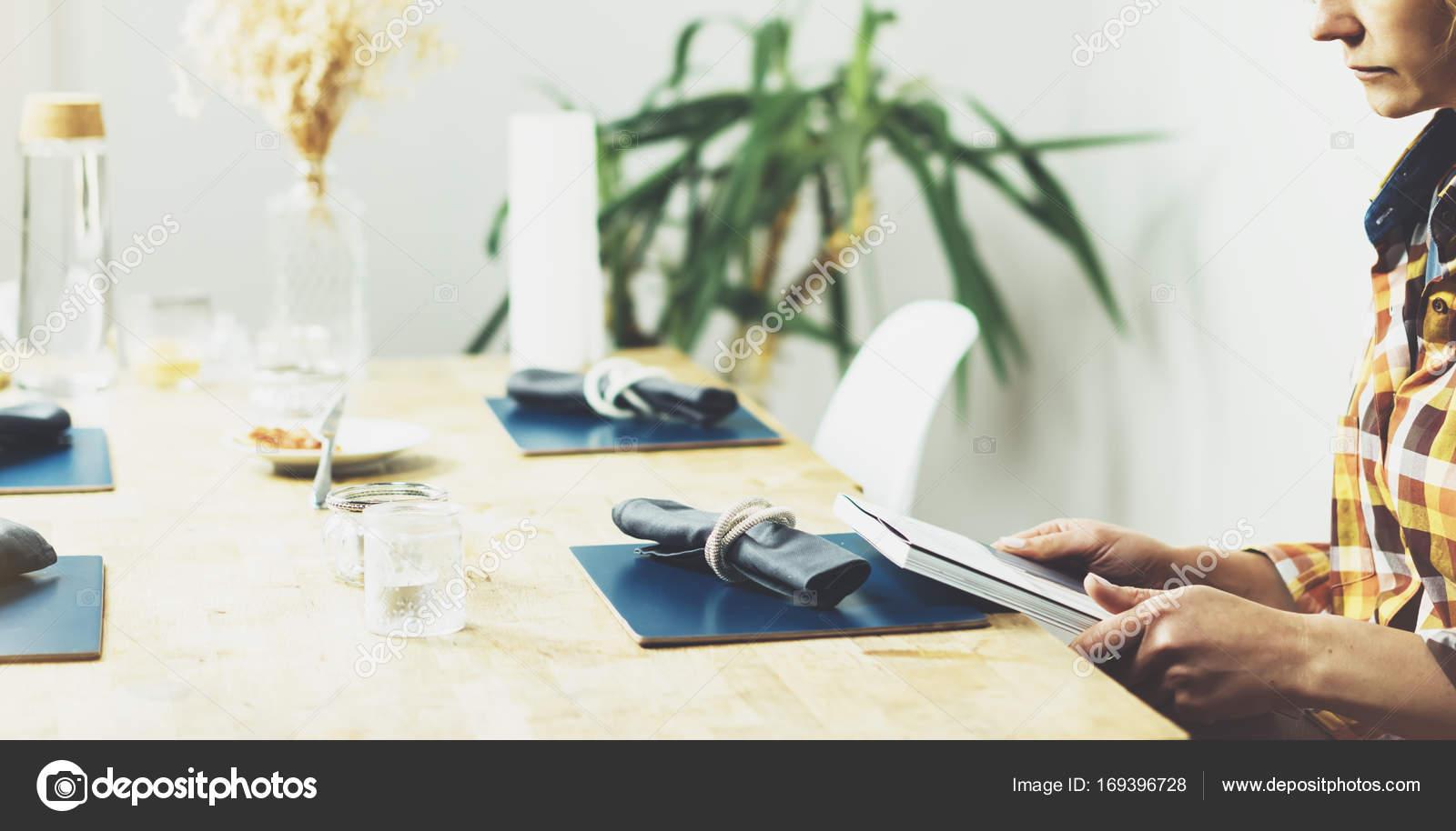 Jong meisje leest boek tijdens ontbijt koffie vrouwelijke handen