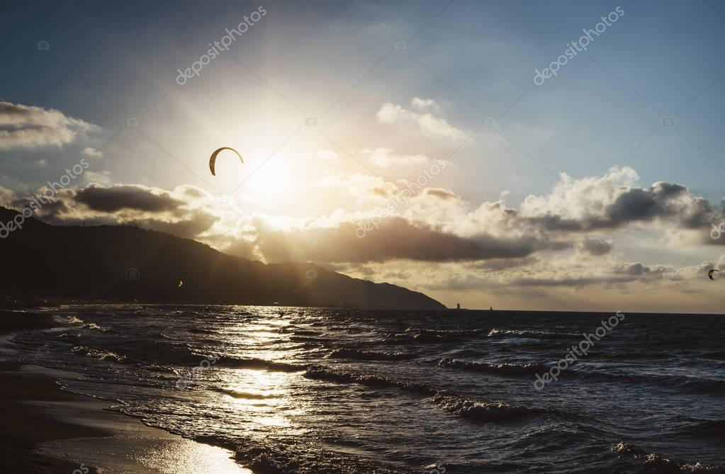 Sunlight sunset on horizon ocean on background seascape atmosphere rays sunrise. Relax view waves sea with kitesurfing on sand beach,  sun light flare nature evening concept, copy space for tex