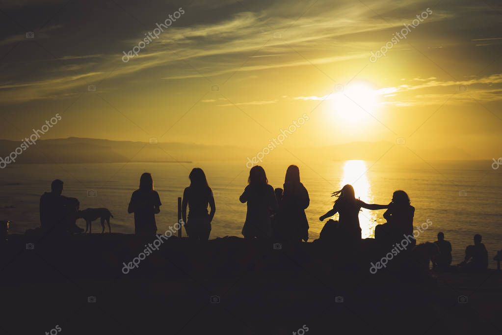 Group of young friends on background beach ocean sunrise, silhouette romantic people dances looking on rear view evening seascape, happy hipster enjoy sunset together, travel holidays vacation, love relax concept