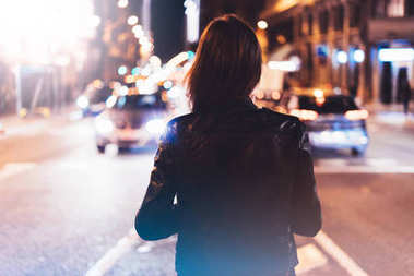 Hipster girl in black leather jacket from back on background illumination glow bokeh light in night atmospheric city, hipster costs at a stop in headlights auto taxi; mockup glitter, lifestyle concept
